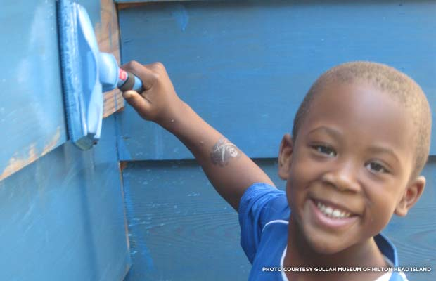 A young volunteer helps to paint The Little House. Credit: Gullah Museum of Hilton Head Island