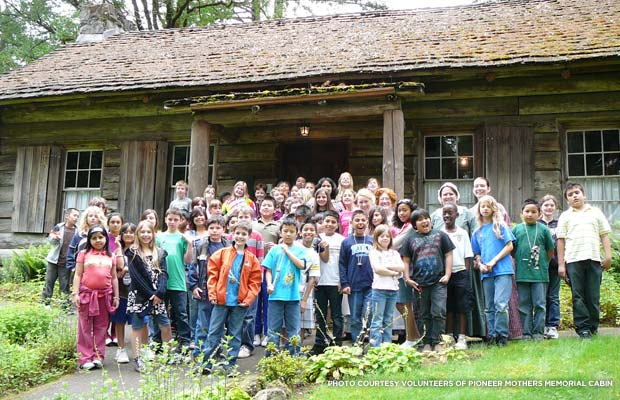 A school group gathers in front of the Pioneer Mothers Memorial Cabin. Credit: Volunteers of the Pioneer Mothers Memorial Cabin