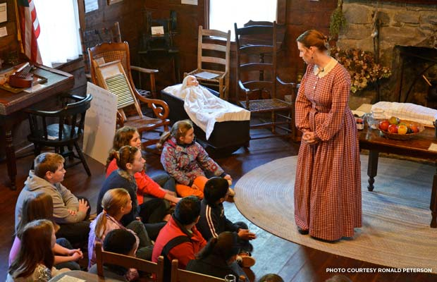 Pioneer Mother Carrie Friedrich hosts a school tour. A local music teacher, she has also brought the music of the pioneers to the cabin for the children to enjoy. Credit: Ronald Peterson