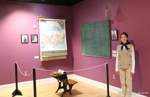 Julia Bache poses with an original Rosenwald School chalkboard. Credit: Lisa Bache