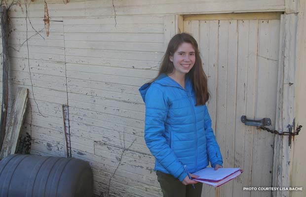 Julia Bache in front of the original Buck Creek School girls' outhouse. Credit: Lisa Bache
