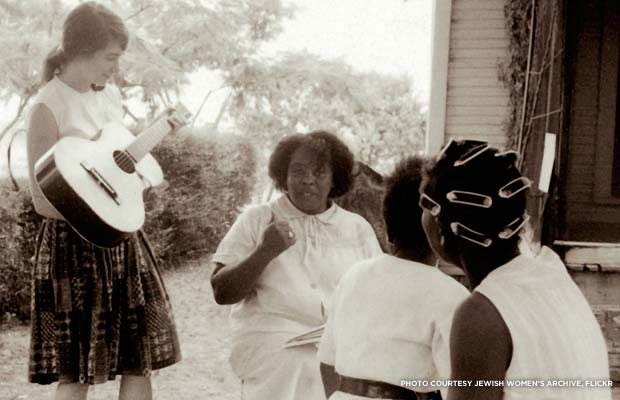 Heather Booth playing guitar for Fannie Lou Hamer during the Freedom Summer Project in Mississippi, 1964. Credit: Jewish Women's Archive, Flickr