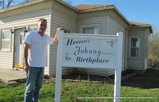 Dan Riedemann, of Nineteenth Century Restorations, LLC, poses with a sign outside Johnny Carson's birthplace before the restoration. Credit: Dan Riedemann/Nineteenth Century Restorations, LLC