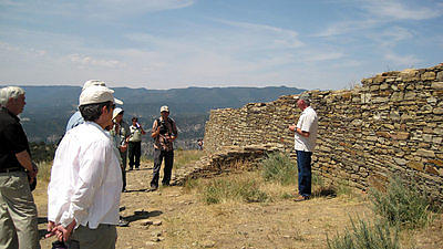 A group tour in front of a prehistoric wall.