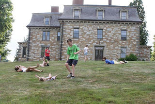 Children rolling down the hill at the Burnett/Garfield House