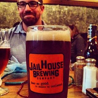 A patron with a drink from the Jailhouse Brewing Company