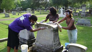 A group of volunteers work together to clean a historic tombstone.