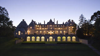 Exterior shot of Oheka Castle lit at night.