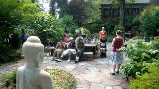 A tour sits in the gardens of the Museum of Tibetan Art
