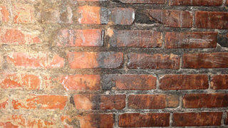 An interior shot of the brick wall in the men's room at Crawford's showing soot from the meat-smoking days.