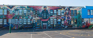 A shot of a mural showing Cesar Chavez painted on a school's facade.