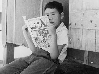 Evacuee boy reading Funnies