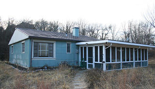 Exterior of blue lustron house with porch view