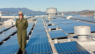 National Park Service Environmental Specialist stands with solar panels