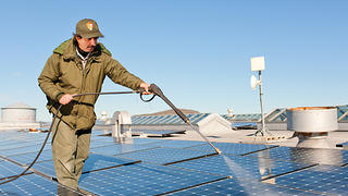 NPS staffer washes the solar panels
