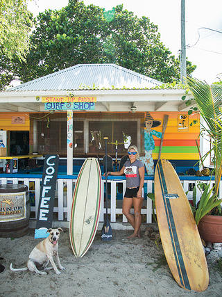Woman and her dog sit outside a surf shop