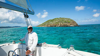 Man stands at the wheel of a sailboat with an island in the background