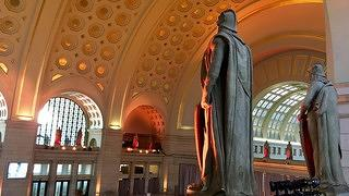View of the gilded c offered ceiling in Union Station from the balcony behind the statues.