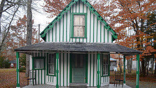 A green striped cottage typical of camp meeting style