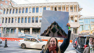 A woman holds a before photo of the Fogarty Building in front of it. Credit: Christian Scully/Design Imaging Studios