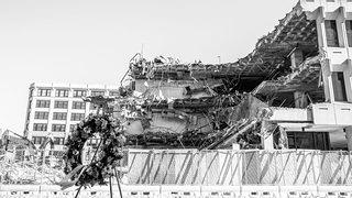 black and white photograph of the partially demolished Fogarty Building with a wreath in the foreground. Credit: Christian Scully/Design Imaging Studios