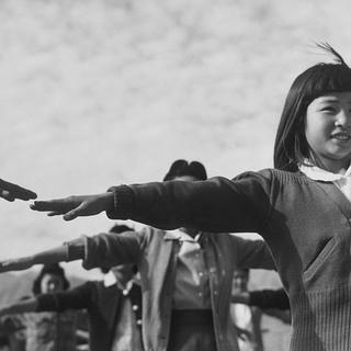 A group of young girls at Manzanar Relocation Center doing calesthenics, 1943.