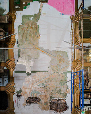 During the theater's restoration process, preservationists carefully chipped away at thick layers of paint covering the murals. They successfully saved three panels.
