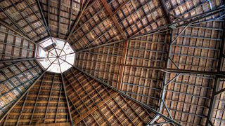 The interior of an octagonal barn shows its roof construction