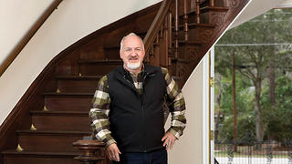 Art Smith in front of original mahogany staircase