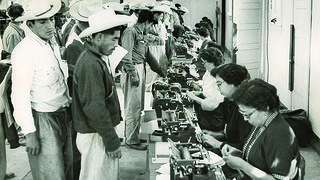A historic photo of braceros in line at the Rio Vista processing center in Texas.