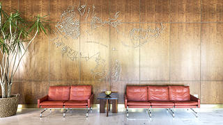 This brass map of Charleston against cherry wood paneling greets visitors when they enter the lobby.
