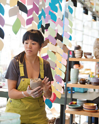A craftsperson at a vendor stand at the Pike Place MarketFront