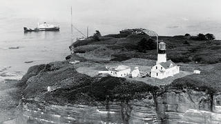 A historic photo of Cape Flattery Lighthouse and Tatoosh Island.