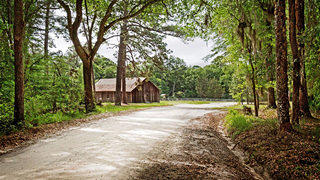 The dirt road leads to a vernacular frame church, Emmaus Primitive Baptist.