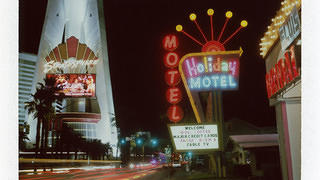 An exterior shot of the Holiday Motel neon sign.