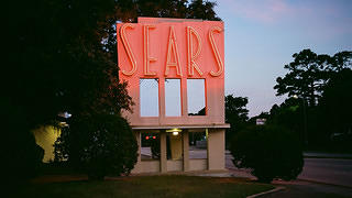 The neon sign of a Sears in Houston.