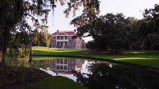 Drayton Hall's exterior, surrounded by willow trees and grounds.