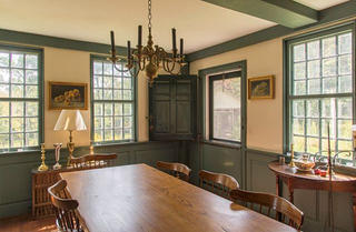 The dining room has green-painted wall panels, chair rail, and trim.