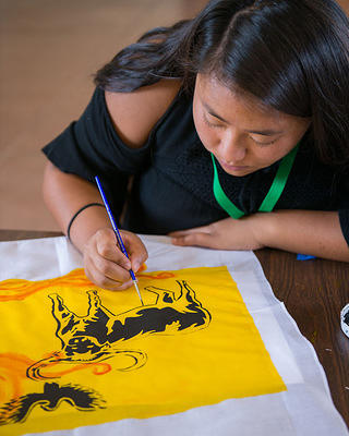 A student creates a painting as part of the Youth Heritage Program.