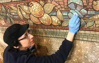 A John Canning conservator works on the pendentives.