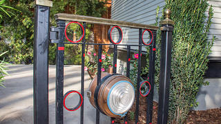 A garden gate built of re-purposed railroad parts.