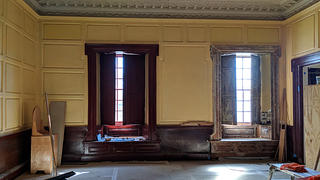 The shutters and architrave surrounding the windows in the main hall before and after restoration. Credit: Kirsten Hower