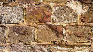Remnants of the yellow color wash on the mortar joints where the construction of the hyphens preserved them.