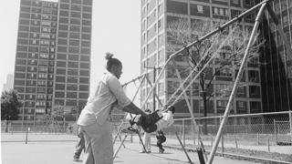 A mother pushes her child on a swing in a playground at Cabrini-Green in 1981.