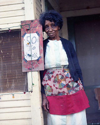 Clementine Hunter at her home, next to a pricing sign.