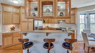 My kitchen features gorgeous floating glass cabinets set above a bar made for entertaining.