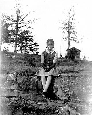Nina Simone, aged 8, sits in the yard outside of her childhood home in Tryon.