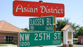 A photo of a red street sign for the Asian District. Below are two green signs marking the intersection of Classen Blvd. and NW 25th St.