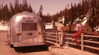 Campers fish by snowcapped mountains next to their vintage Airstream.
