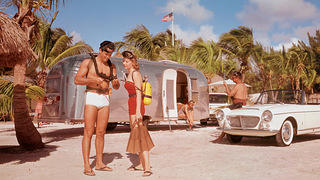 Campers decked out in vintage swimwear prepare for a beach day by their vintage Airstream.